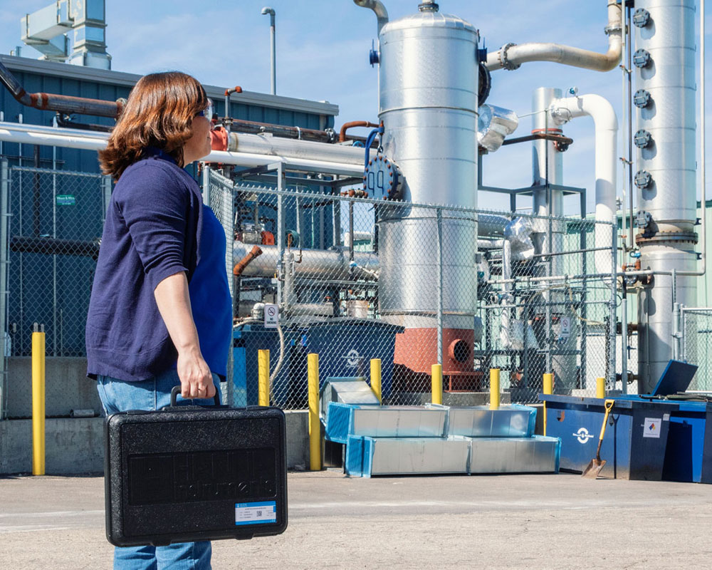 Woman with testing equipment outside a petrochemical facility.