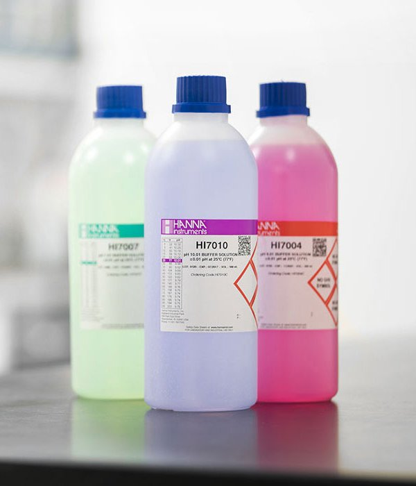 Three colorful bottles of buffer solutions.